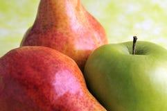 Peras y manzana verde Imagen de archivo libre de regalías