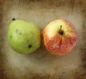 Peras y manzanas orgánicas en una vieja tajadera de piedra rústica Foto de archivo libre de regalías