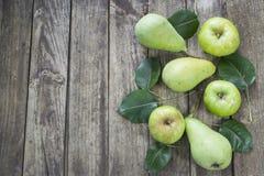 Peras y manzanas verdes con las hojas en la tabla vieja, de madera Alto ANG Fotos de archivo libres de regalías