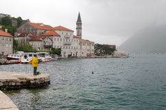 Perast. Fisherman. PERAST, MONTENEGRO - MAY 17, 2013: A man fishes in the harbor of Perast, a small town on the Bay of Kotor, Montenegro. On May 17, 2013, in Royalty Free Stock Photo