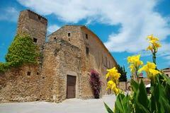 Peratallada, Costa Brava, Catalonia, Spain. Peratallada, Costa Brava, Catalonia, Spain: Famous medieval square at daytime with flowers Royalty Free Stock Photo