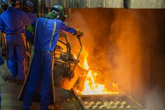 Perator som häller smält metall i automatisk rollbesättninglinje i foundr royaltyfri bild