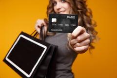 Perca-acima o retrato da mulher moreno nova feliz que guarda o cartão de crédito e sacos de compras coloridos, olhando a câmera foto de stock