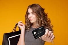 Perca-acima o retrato da mulher moreno nova feliz que guarda o cartão de crédito e sacos de compras coloridos, olhando a câmera fotos de stock