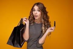 Perca-acima o retrato da mulher moreno nova feliz que guarda o cartão de crédito e sacos de compras coloridos, olhando a câmera fotografia de stock