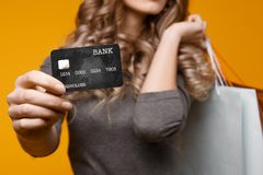 Perca-acima o retrato da mulher moreno nova feliz que guarda o cartão de crédito e sacos de compras coloridos, olhando a câmera imagem de stock
