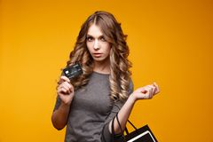 Perca-acima o retrato da mulher moreno nova feliz que guarda o cartão de crédito e sacos de compras coloridos, olhando a câmera fotografia de stock royalty free