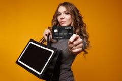 Perca-acima o retrato da mulher moreno nova feliz que guarda o cartão de crédito e sacos de compras coloridos, olhando a câmera fotos de stock royalty free
