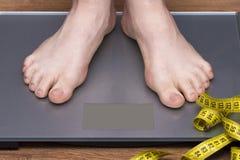 Perca o conceito do peso com a pessoa em quilogramas de medição de uma escala Foto de Stock Royalty Free
