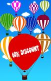 60 PERCENT DISCOUNT written on hot air balloon with a blue sky background. Stock Photography