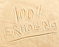 100 percent Erholung drawn in beach sand. 100 percent Erholung German text drawn in beach golden sand conceptual of relaxation, summer vacations and travel Royalty Free Stock Image