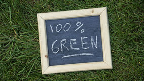 100 percent green. Written on a chalkboard in the nature Stock Photography
