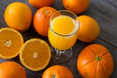 100 percent natural orange juice in a glass. Natural orange juice in a glass on top of a wooden table Stock Image