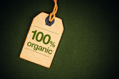 100 Percent Organic Food on Price Label Tag. 100 Percent Organic Food on Vintage Price Label Tag Label on Green Grunge Textured Backgroundas, Top View Royalty Free Stock Image