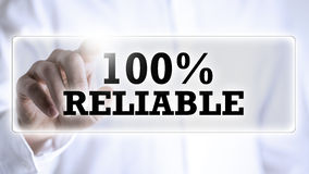100 percent Reliable on a virtual screen. Businessman pressing a navigation bar on a virtual screen or interface with the words 100 percent Reliable conceptual Royalty Free Stock Images