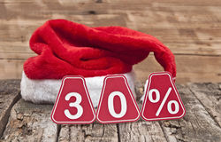 30 percent with santa hat. On old wooden background Stock Image