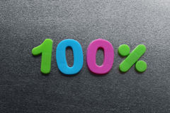 100 percent spelled out using colored fridge magnets Stock Images