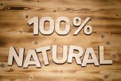 100 percenten NATUURLIJKE woorden die van houten blokletters op houten raad worden gemaakt stock foto