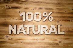 100 percenten NATUURLIJKE woorden die van houten blokletters op houten raad worden gemaakt stock afbeeldingen