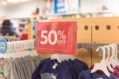 50 percenten van verkoopteken over kleren bij de opslag van de babykleding met klant het winkelen royalty-vrije stock afbeeldingen