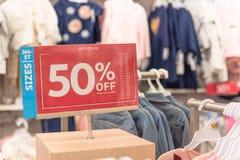 50 percenten van verkoopteken over kleren bij de opslag van de babykleding met klant het winkelen stock foto