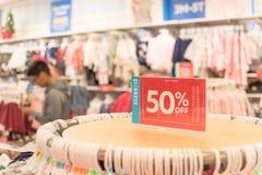 50 percenten van verkoopteken over kleren bij de opslag van de babykleding met klant het winkelen stock afbeelding