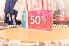 50 percenten van verkoopteken over kleren bij de opslag van de babykleding met klant het winkelen royalty-vrije stock fotografie