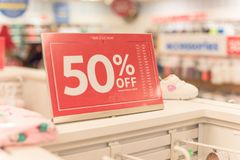 50 percenten van verkoopteken over kleren bij de opslag van de babykleding met klant het winkelen stock afbeeldingen