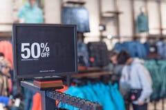 50 percenten van verkoopteken over kleren bij warenhuis met klant het winkelen stock afbeeldingen