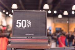 50 percenten van verkoopteken over kleren bij warenhuis met klant het winkelen royalty-vrije stock foto's