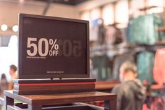 50 percenten van verkoopteken over kleren bij warenhuis met klant het winkelen royalty-vrije stock foto