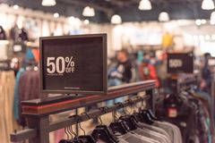 50 percenten van verkoopteken over kleren bij warenhuis met klant het winkelen stock fotografie