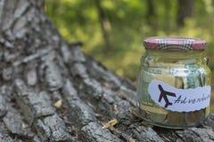 Perception d'argent dans un pot en verre pour l'aventure Photos stock