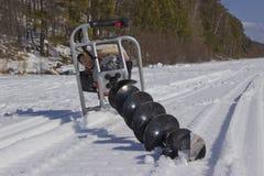 Perceuse de moteur pour pêcher dans la neige images libres de droits