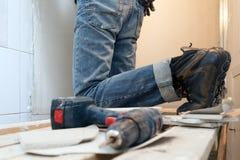 Perceuse poussiéreuse de construction professionnelle de plan rapproché, perforateur sur le fond de l'ouvrier, outils de bâtiment image libre de droits