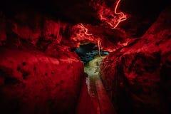 Percez un tunnel dans une caverne rampante foncée naturelle, allumée par la lumière rouge Photos libres de droits