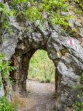 Percez un tunnel sur le chemin de hausse en parc national Cheile Nerei Roumanie Rouge a Photo libre de droits