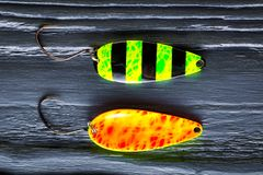 Perch baits.Perch baits on black wooden table closeup. Fishing baits stock photography