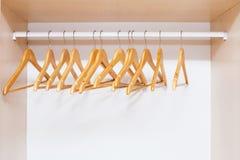 Perchas de capa de madera en el carril de la ropa Imagen de archivo