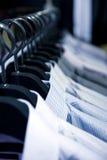 Perchas de paño con las camisas Imágenes de archivo libres de regalías