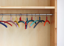 Perchas de ropa coloridas en armario Imágenes de archivo libres de regalías