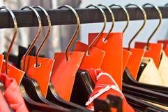 Perchas de ropa con las escrituras de la etiqueta rojas de la venta en un departamento Fotos de archivo libres de regalías