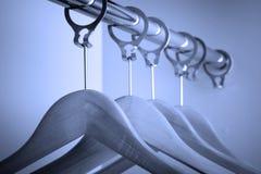 Perchas de ropa en azul Fotografía de archivo libre de regalías