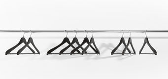 Perchas de ropa negras en el fondo blanco Imagen de archivo