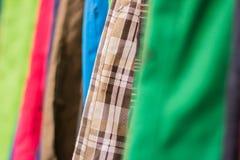 Perchas en la tienda de la ropa DOF bajo Fotos de archivo