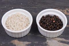 Percorra o sal e grãos de pimenta cinzentos em ramekins smal na ardósia cinzenta Imagem de Stock Royalty Free