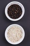 Percorra o sal e grãos de pimenta cinzentos em ramekins smal no preto matte Imagens de Stock Royalty Free