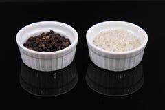 Percorra o sal e os grãos de pimenta cinzentos s em ramekins pequenos no reflectiv Foto de Stock Royalty Free