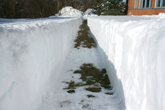 Percorso accanto a costruzione con la rimozione di neve dopo la bufera di neve Fotografie Stock