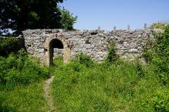 Percorso del piede al portone della parete di rovina del castello immagini stock